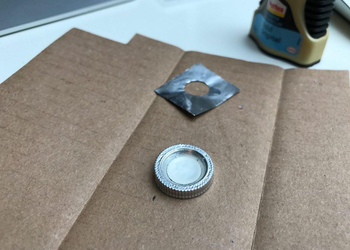 De transparante lens die in één van de knoppen van het lightsaber bevestig is. Onder deze doorzichtige print zit een stukje aluminiumfolie voor een interessant visueel effect.
